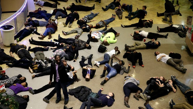 "Protesters stage a ""die in"" inside Chesterfield Mall in Chesterfield, Mo. The crowd disrupted holiday shopping at several locations on Friday amid a protest triggered by a grand jury's decision not to indict the police officer who fatally shot Michael Brown in nearby Ferguson."