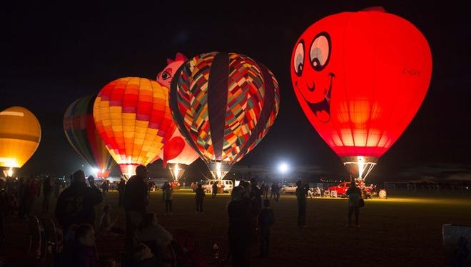 Balloons sit grounded during the Desert Glow event at the Arizona Balloon Classic at the Fear Farm Sports & Entertainment Complex on Friday, Jan. 23, 2015, in Phoenix.