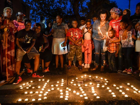 Friends, family and neighbors of 16-year-old Deberianah Begley gather for a candle light vigil at the James Cayce Public Housing Development in Nashville, Tenn., Monday, Oct. 9, 2017.