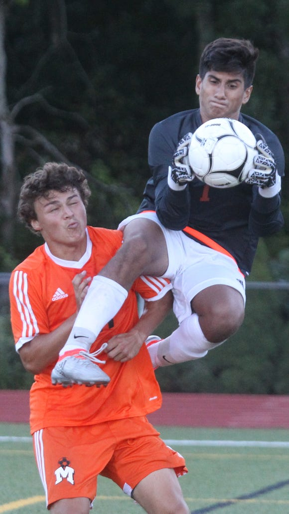 Yorktown goalie Mauricio Arango grabs the ball before Mamaroneck's Cole DiCicco can get to it during their game at Yorktown Sept. 12, 2016. Yorktown won 4-2.