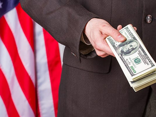 businessman-holding-dollars-beside-flag-square.jpg