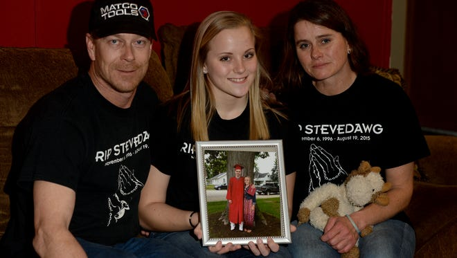 Caleb Stevens' father Joshua, sister Megan and mother Tara Stevens, right, hold a photo of Caleb at their home, Thursday, March 10, 2016.