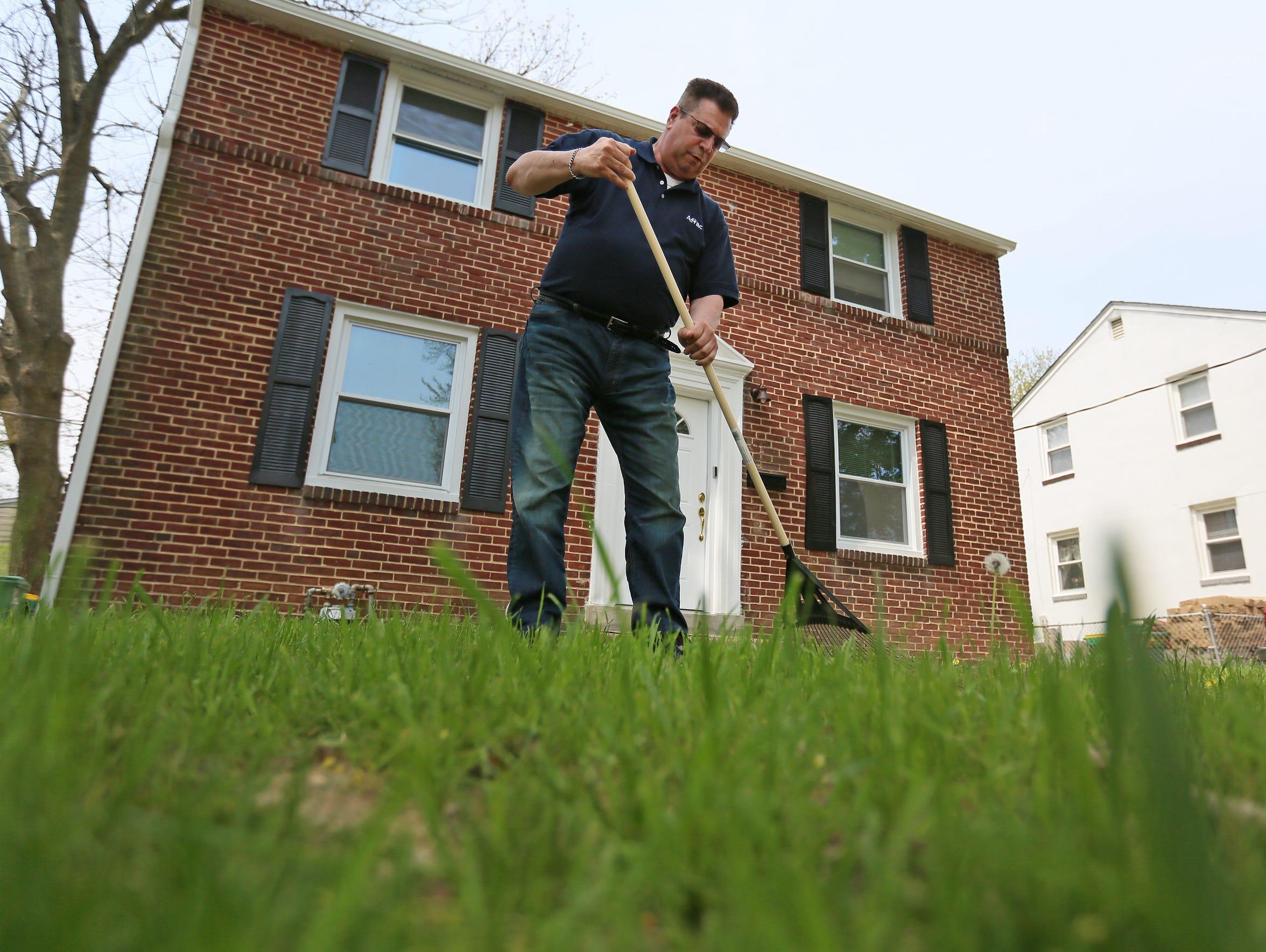 Ron Barisano, who has diabetes, rakes the lawn of his