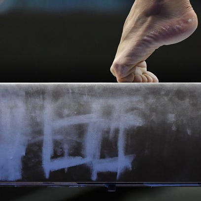 Detail view of a gymnast's foot on the balance beam