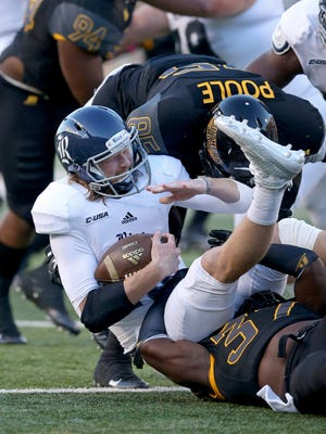 Southern Miss defensive lineman Ja'Boree Poole and linebacker Sherrod Ruff (37) sack Rice quarterback Tyler Stehling in the first quarter of their game Saturday at M.M. Roberts Stadium in Hattiesburg.