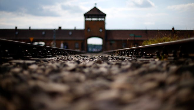 In this June 25, 2015 file photo railway tracks lie in front of the main entrance of former Auschwitz-Birkenau Nazi death camp in Oswiecim, Poland.