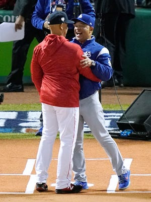 Boston Red Sox manager Alex Cora, left, greets Los Angeles Dodgers manager Dave Roberts at home plate before Game 1 of the World Series baseball game Tuesday, Oct. 23, 2018, in Boston. (AP Photo/Elise Amendola)