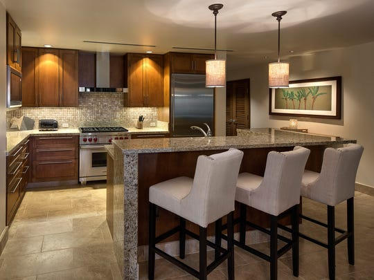 Kitchens at the Ritz-Carlton Residences come with stainless steel appliances, stone countertops and chestnut cabinetry. The backsplash behind the stove is limestone and granite.