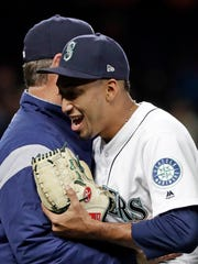 Mariners closer Edwin Diaz, right, embraces manager Scott Servais after a win over the Oakland Athletics last month in Seattle. Servais has promised to get his hair cut in the same style as Diaz if his closer reaches 50 saves on the season. Diaz already has 11.
