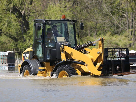 Ralph Masters drives  a Caterpillar through high water at R.T. Masters on Empire Boulevard.  The company had to rent the unit to be able to drive through the rising water of Irondequoit Creek, which has overflowed its banks and is flooding the business.