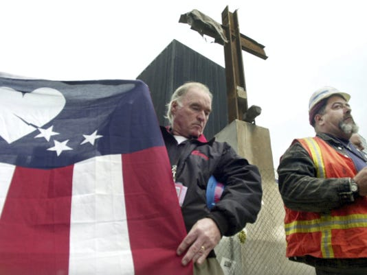 FILE - In this Oct. 4, 2002, file photo, construction workers Terence McBreen, left, and Frank Silecchia, right, are shown during the rededication of the steel beam cross at the World Trade Center site in New York City. Silecchia discovered the beam cross as he searched for survivors in the rubble of 6 World Trade Center on Sept. 13, 2001. Pieces of steel from the twin towers have been parceled out to all 50 states and eight countries for memorials and museum exhibits and were used in the construction of the U.S. Navy ship USS New York. Of 2,200 pieces of steel preserved in an airplane hangar in New York City, there are fewer than 30 left. (AP Photo/Bebeto Matthews, File)
