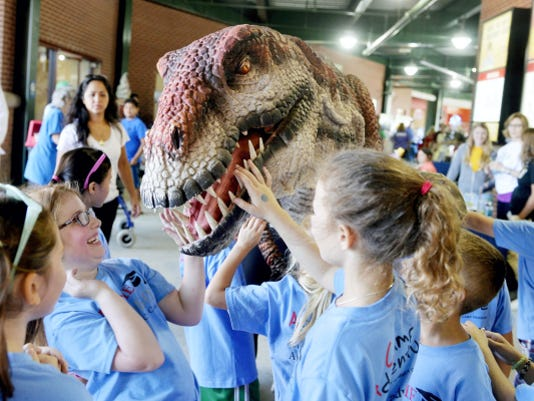 "On York Revolution Camp Day, campers gather around an animatronic dinosaur Thursday at Santander Stadium. <a href=""https://youtu.be/PsxcjFj-H1M"">Click here to watch video.</a>"
