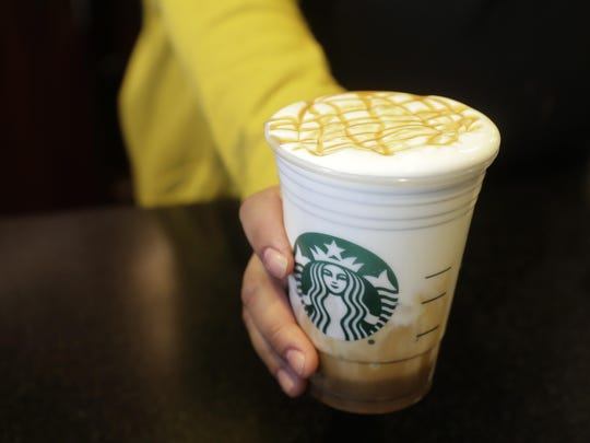 In this March 5, 2019, photo, a Starbucks barista moves a finished Cloud Macchiato coffee drink to the counter in the company's headquarters building in Seattle's SODO neighborhood. The dramatic plunge in coffee prices has gotten so bad that it's threatening specialty blends used by fancy coffee shops like Starbucks.