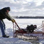Brian Rach and Ken Juckem, both of Chilton, push away a block of ice before moving a shanty over the hole in preparation for Saturday's opening of sturgeon spearing on Lake Winnebago.