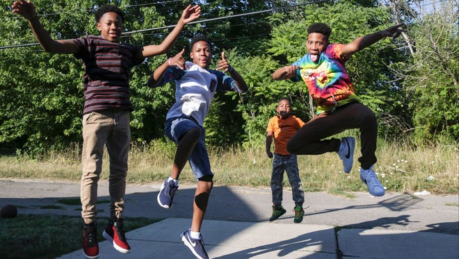 Maximillian, 14, Ellington, 17,  Judah Smith, 7, and Carlito Smith, 16, pose for a portrait in their backyard at their home on Detroit's east side on Aug. 2, 2016. The boys told their story as part of the Solutions project for the Free Press.