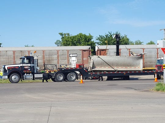 The back of a truck that collided with a train Monday, July 31, is put on a trailer to be carried away from the scene.