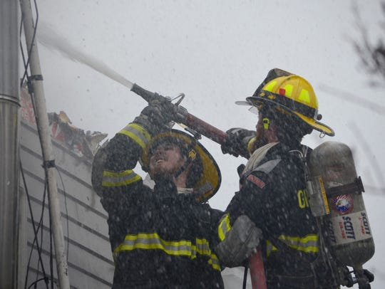Firefighters hose down the walls of a South Hero home
