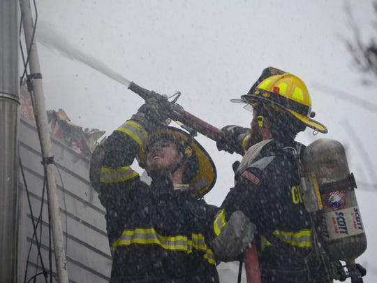 Firefighters hose down the walls of a South Hero home on Wednesday.