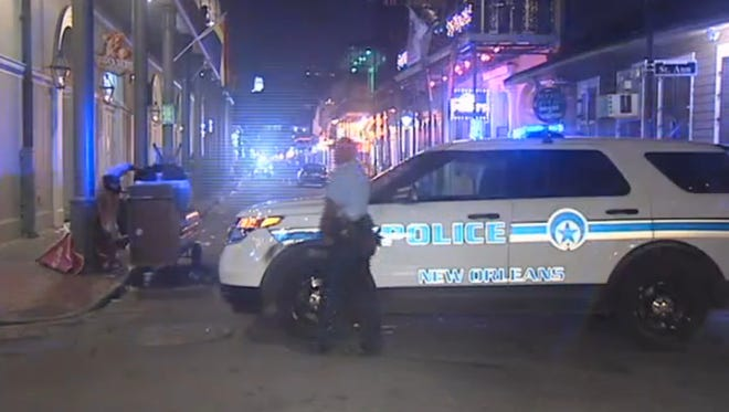 New Orleans police officers investigate a shooting incident on Bourbon Street on June 29.