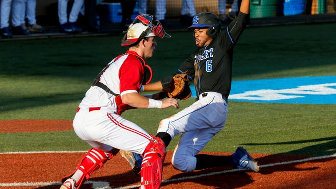 Kentucky's Tristan Pompey slides past NC State's Andy Cosgrove to score the first run of the game. June 3, 2017
