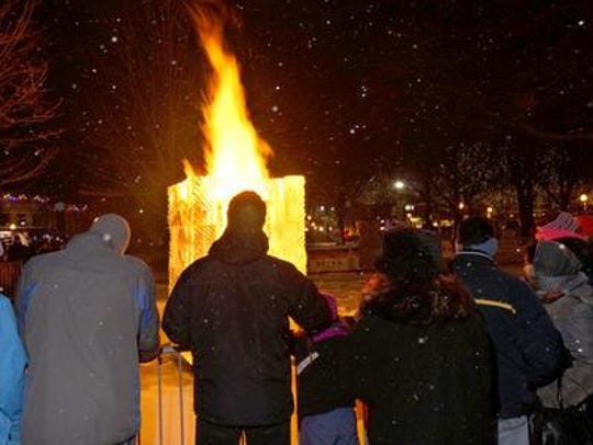 A fire and ice tower lights up the sky at Kellogg Park