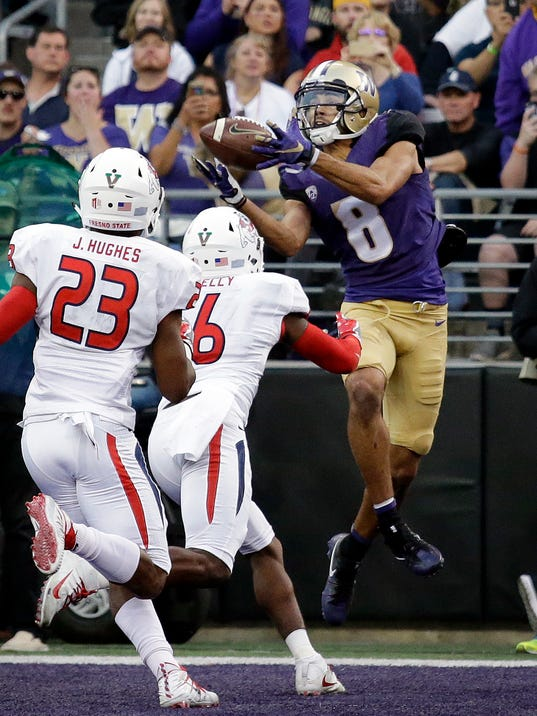 Washington's Dante Pettis (8) catches a touchdown pass in the end zone as a pair of Fresno State defenders move in in the first half of an NCAA college football game, Saturday, Sept. 16, 2017, in Seattle. (AP Photo/Elaine Thompson)