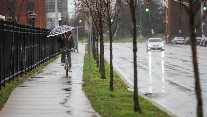 Jonathon Wakefield rides his bike down Vine Street in heavy rain.