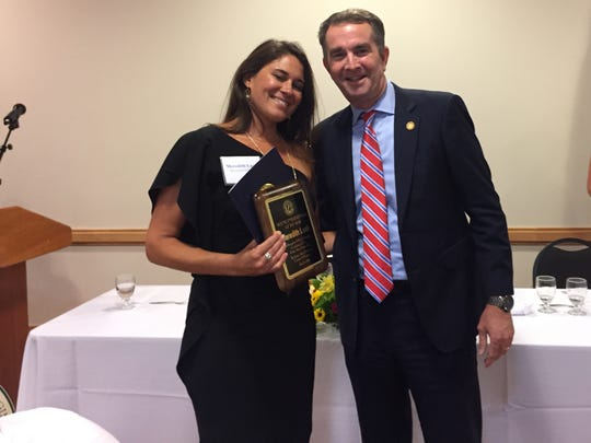 Gov. Ralph Northam presents the Young Entrepreneur of the Year award to Meredith Lusk at the Eastern Shore of Virginia Chamber of Commerce annual meeting on Monday, July 23, 2018 in Melfa, Virginia.