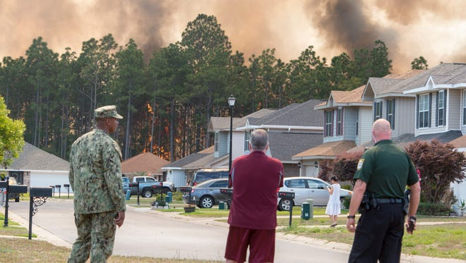Residents and law enforcement watch as firefighters fight a wildfire burning in the woods behind the homes on Weatherstone Circle in Pensacola on Monday, May7, 2018.