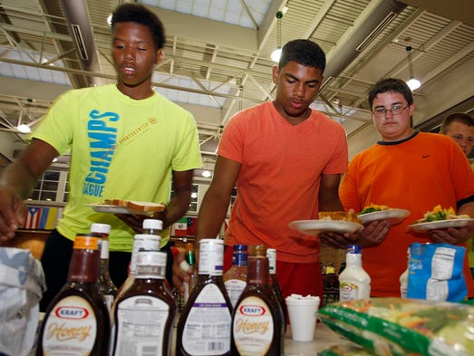 From the left, Roberto Galbin, CJ Oliver, and Brandon Waits gather their evening meal on August 8, 2014 at Central High's week long football camp in which the players stayed overnight at the school.