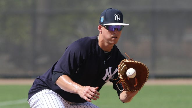 At first base, Tyler Austin makes a play on a ground ball during defensive drills.