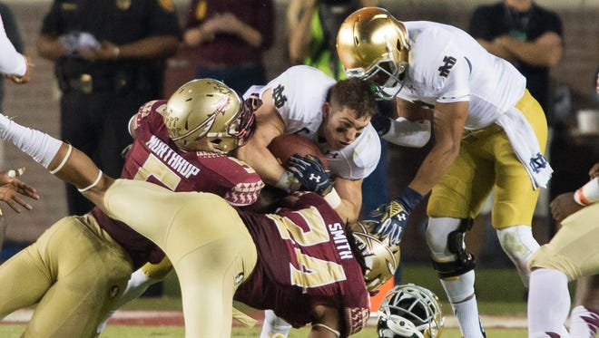 Notre Dame Fighting Irish running back Cam McDaniel (33) loses his helmet after being hit by Florida State Seminoles linebacker Reggie Northrup (5) and linebacker Terrance Smith (24) in the third quarter at Doak Campbell Stadium.