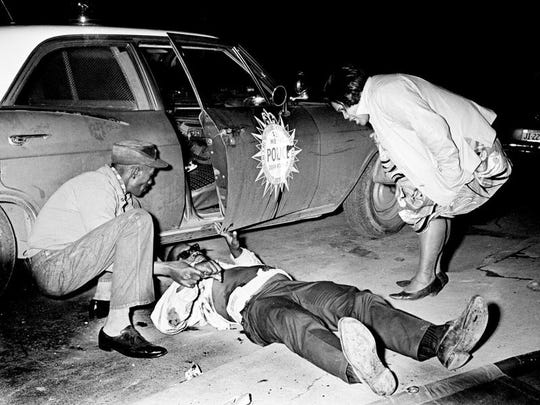 A couple of friends check on Elvis Fleming, center, 50, of Pecan Street, after he was wounded during a Metro police gun battle April 4, 1968. Fleming and 13-year-old Anthony Webster were hurt when police were summoned to 22nd Ave. and Osage St. to check a complaint that an armed person was threatening residents during rioting after the assassination of Rev. Martin Luther King Jr.