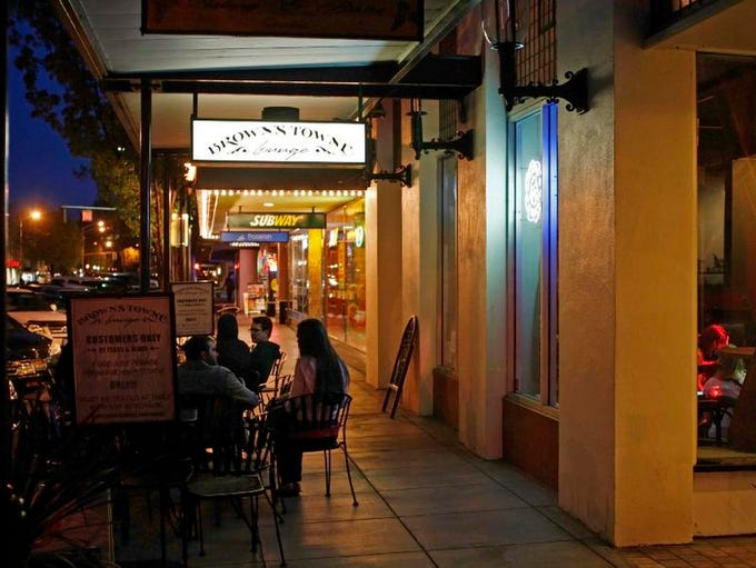 Patrons take advantage of the outdoor seating at Brown's Towne Lounge, on Liberty Street downtown, on Wednesday, April 10, 2013. The lounge is celebrating it's fifth birthday all month long.