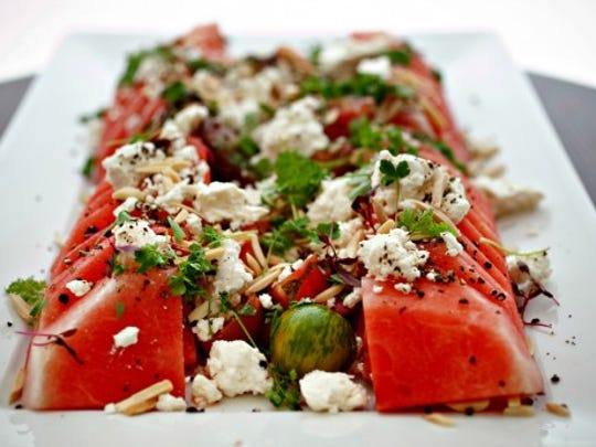 This salad contains watermelon, feta cheese and almonds.