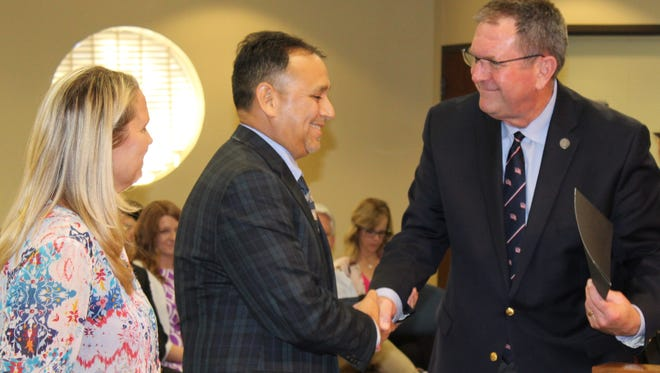 Tim de la Vega is congratulated by state Rep. and former Abilene ISD board member Stan Lambert after Lambert installed him as Place 1 trustee on Monday night at One AISD Center. With de la Vega is his wife, Gayla.