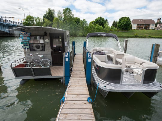 The floating office for Michigan Boat Rentals is docked next to one of the rental pontoon boats offered by the company on Monday, June 4, 2018, on the Black River in Port Huron. The company offers rentals on several pontoon boats, kayaks and stand-up paddle boards.
