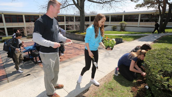 Paul Davis, a teacher and adviser for the White Plains High School Advocates for the Earth Club, hands flowers to ninth-grader Sydney Barest as they plant flowers in the senior courtyard on Earth Day.