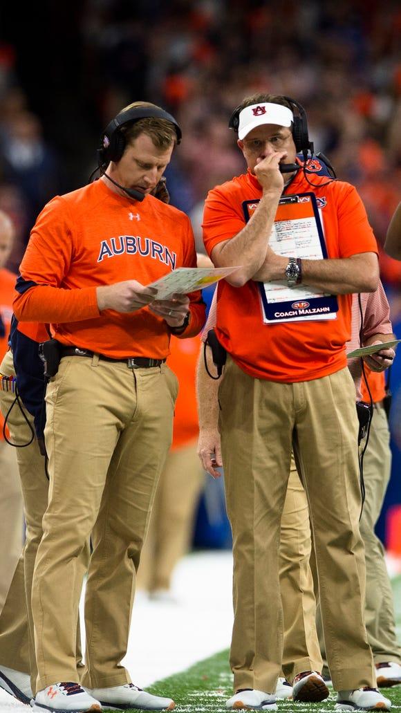 Auburn head coach Gus Malzahn, right speaks to Auburn