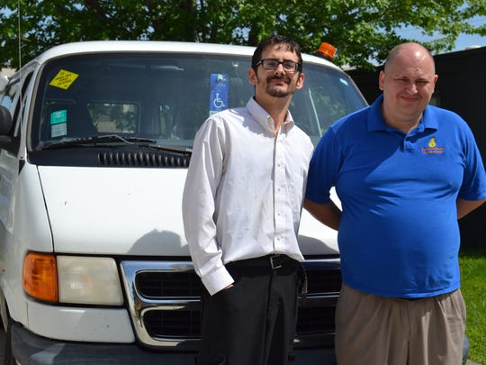 Bishop Andy Roberts and Bishop Lee Bowling stand next to the van they use as a public transportation ministry.