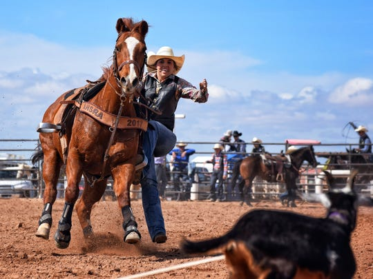 New Mexico State University rodeo athlete Baylee Johnston, of Prescott, Arizona, dismounts her horse in the goat tying event at the Casa Grande, Arizona college rodeo.