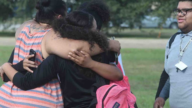 Family members with a sigh or relief hug their children after they are released from lockdown.