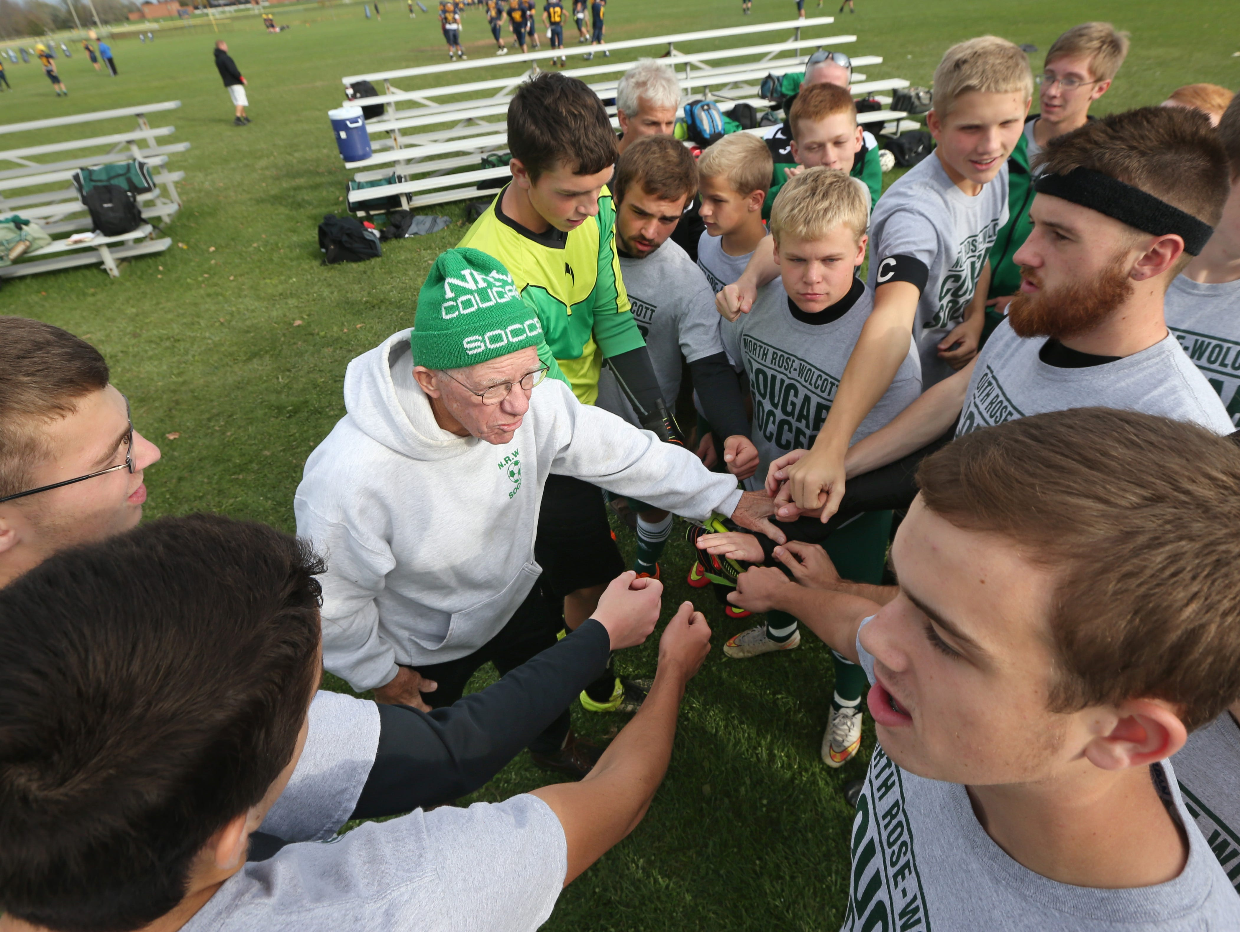"""All hands join in with head coach Gordon """"Scotty"""" Martin as he gives final instructions to his North Rose-Wolcott boys varsity soccer team before a scrimmage at Wayne Central Tuesday, Oct. 20, 2015 in Ontario. After 44 years of coaching, Martin is retiring at the end of the season."""