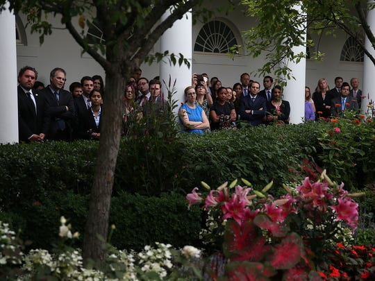 White House staff gather in the colonnade to listen