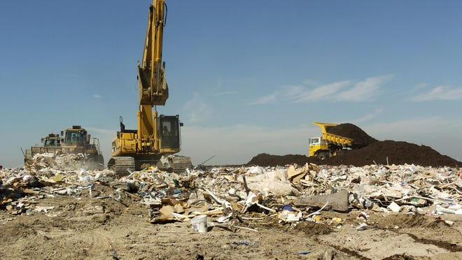 Bulldozers, a hydraulic excavator and a large dumptruck move debris and dirt at the Gulf Coast Landfill. The EPA released figures in 2010 showing Americans dump about 11 million tons of textiles in landfills every year.