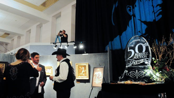 C.M. Russell Museum Executive Director Tom Figarelle, second from left, makes the rounds during The Russell First Strike Auction earlier this year.