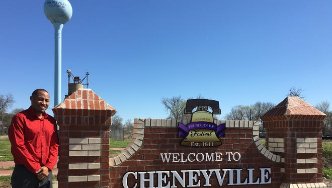 Cheneyville Mayor Derrick Johnson stands by a sign welcoming Highway 71 motorists to his town.