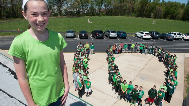 Gillian Blades, 12, gets a bird's-eye view Monday as fellow students at West Deptford Middle School — dressed mostly in green, her favorite color — stand in formation to help celebrate her 10 years being cancer-free.
