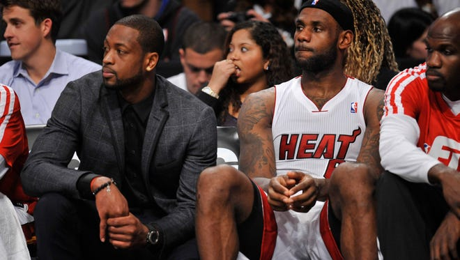 Miami Heat small forward LeBron James (6) and shooting guard Dwyane Wade (suit) understand having their minutes limited, but they don't like it.