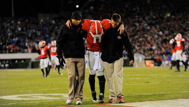 Georgia quarterback Aaron Murray is helped off the field after injuring his knee in a win against Kentucky.